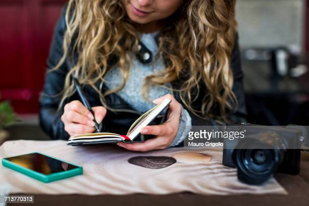 woman at cafe writing in notebook - authors photos et images de collection