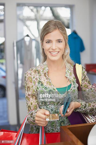 Woman at cashier in store using credit card to pay and smiling