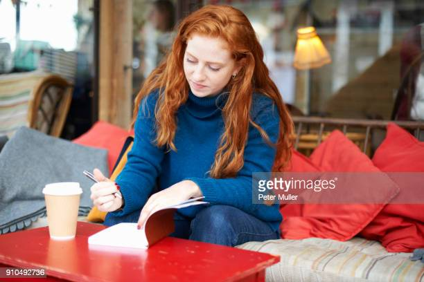 Woman at coffee shop writing in notepad