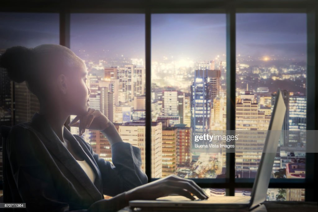 Woman at computer watching city : Stock Photo