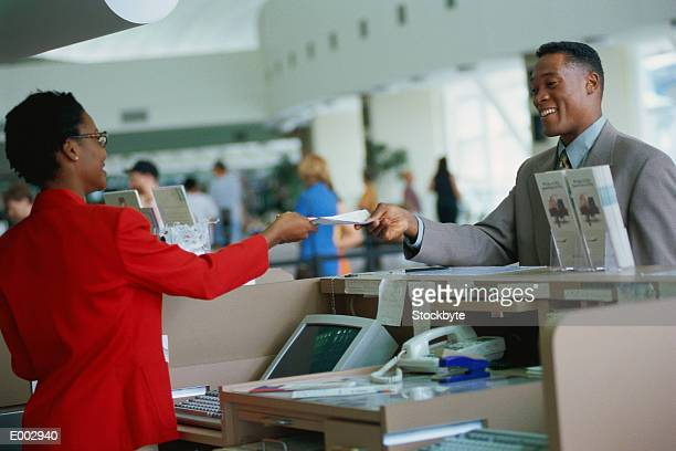 Woman at counter handing airline tickets to man