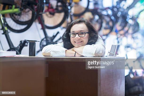 woman at counter in bicycle shop looking at camera smiling - sigrid gombert stock pictures, royalty-free photos & images