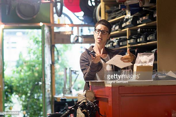 woman at counter in bicycle workshop holding bike part and paperwork - sigrid gombert stock pictures, royalty-free photos & images