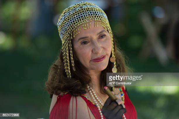 A woman at Dardanella a Great Gatsby Lawn party holds a fake cigar on the lawn near the National Cathedral in Washington DC on September 23 2017...