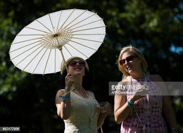 A woman at Dardanella a Great Gatsby Lawn party holds up an umbrella on a lawn near the National Cathedral in Washington DC on September 23 2017...