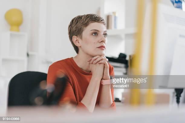 woman at desk in office looking at computer screen - variable schärfentiefe stock-fotos und bilder