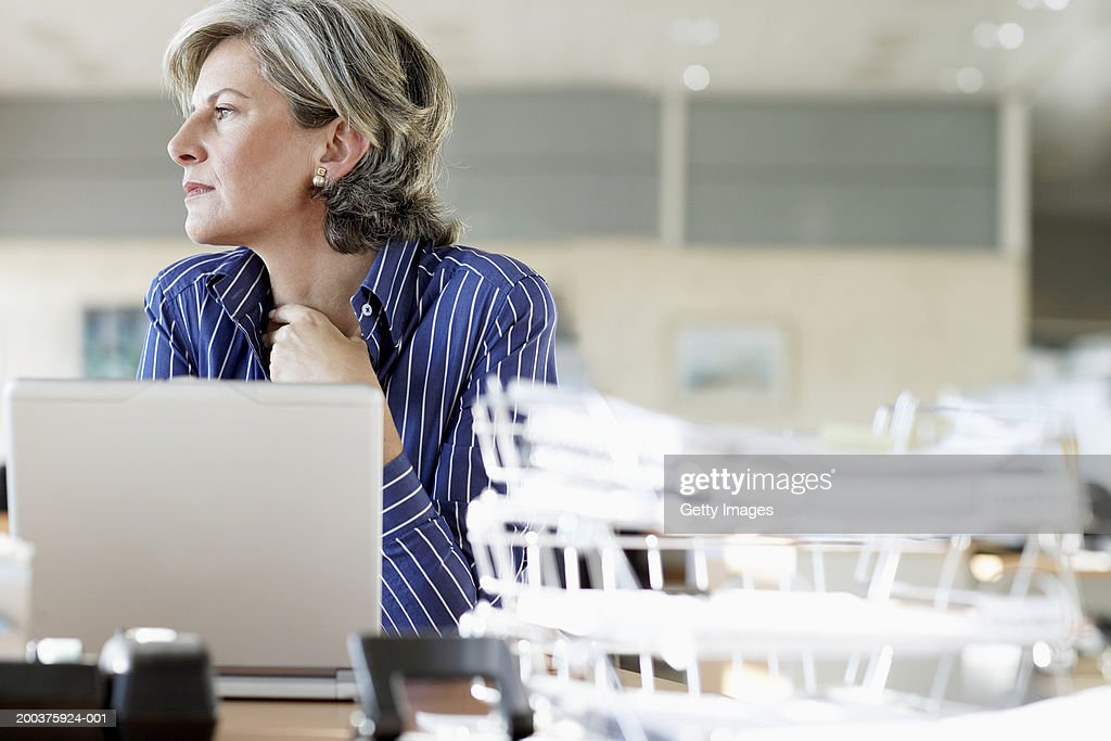 Woman at desk in office, low angle view : Stock Photo