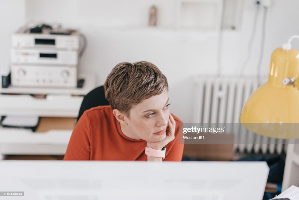 Woman at desk in office thinking : Stock Photo