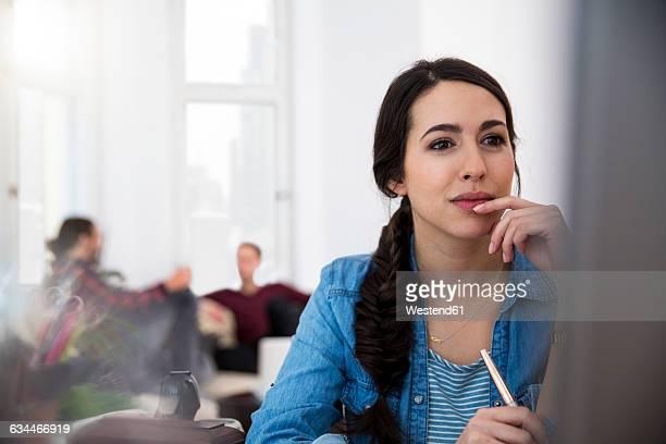 woman at desk looking at computer monitor - gründer stock-fotos und bilder
