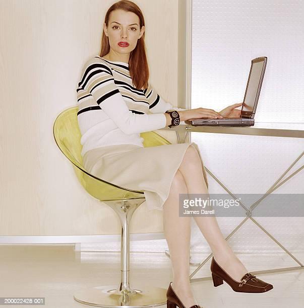 woman at desk using laptop computer, portrait - スカート ストックフォトと画像