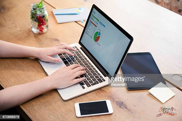 Woman at desk using laptop working on calculation