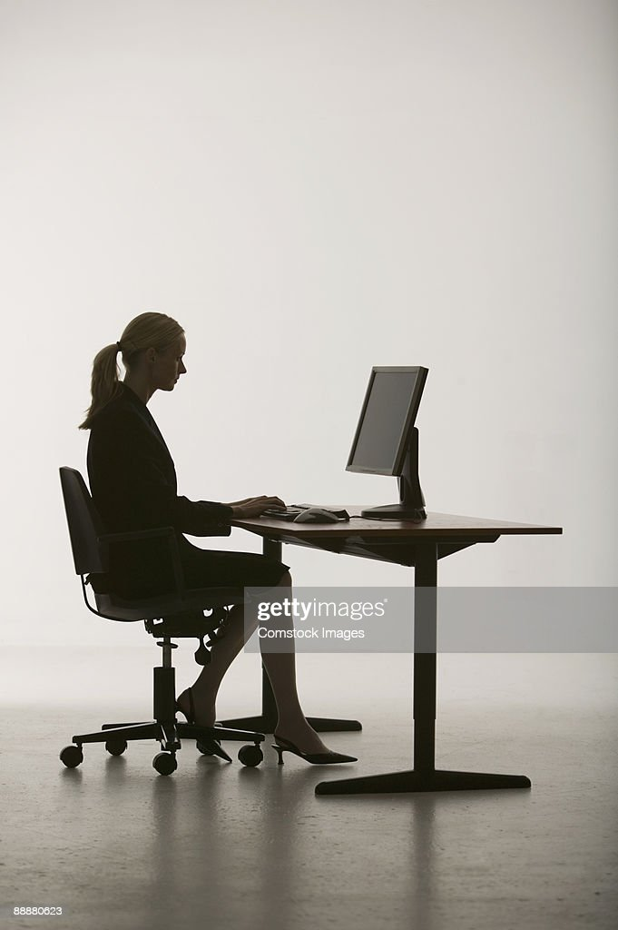 Woman at desk working on computer : Stock Photo