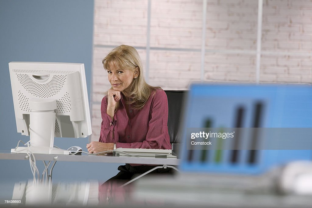 Woman at desktop computer with growth chart on laptop in foreground : Stockfoto