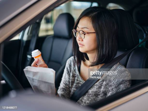 woman at drive-through pharmacy - drive through stock pictures, royalty-free photos & images