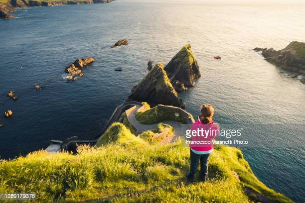 woman at dunquin pier, ireland. - travel stock pictures, royalty-free photos & images