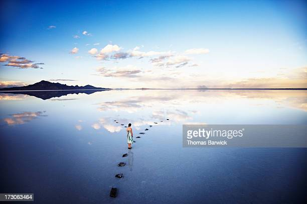 woman at fork in stone pathway in lake at sunset - grand horizons stock pictures, royalty-free photos & images