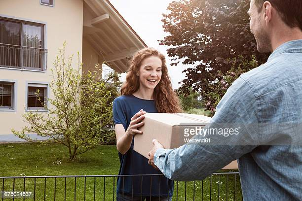 Woman at garden fence receiving parcel