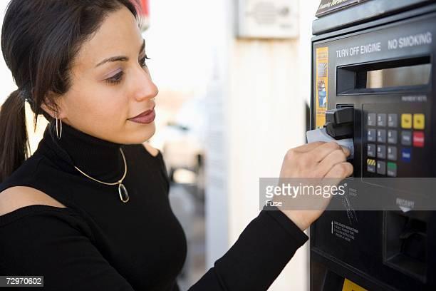 woman at gas pump payment kiosk - セルフサービス ストックフォトと画像