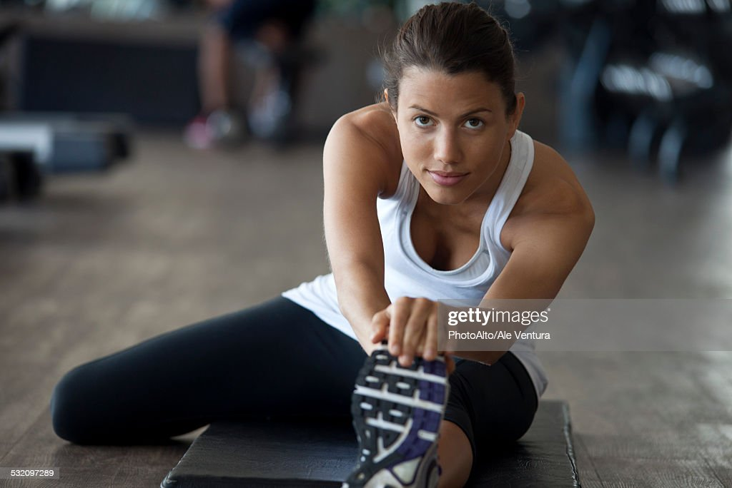 Woman at gym warming up with leg stretches : Stock Photo
