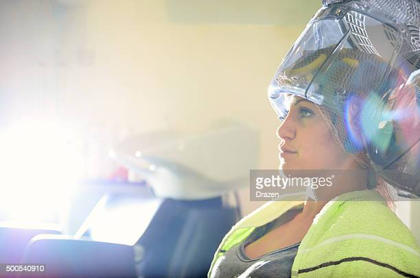 Woman at hair dresser, drying her curly hair under hood