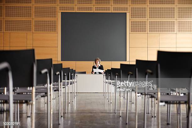 Woman at head of empty conference hall