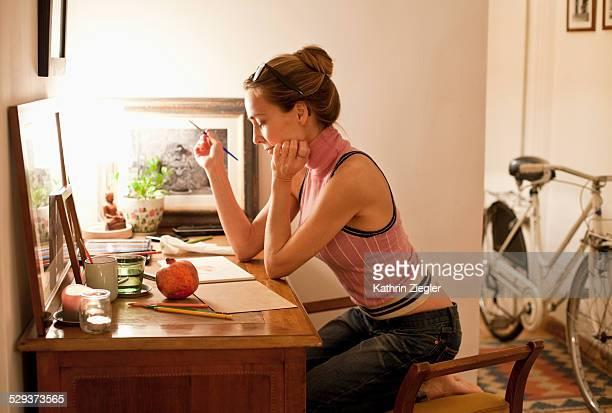 woman at her desk at home, painting - solo una donna matura foto e immagini stock