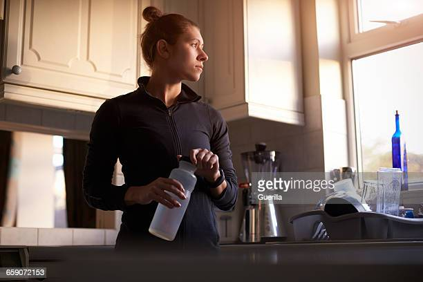 woman at home drinking from water bottle before run - home run ストックフォトと画像