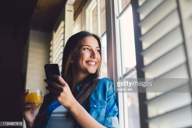woman at home drinking juice and texting - shutter stock pictures, royalty-free photos & images