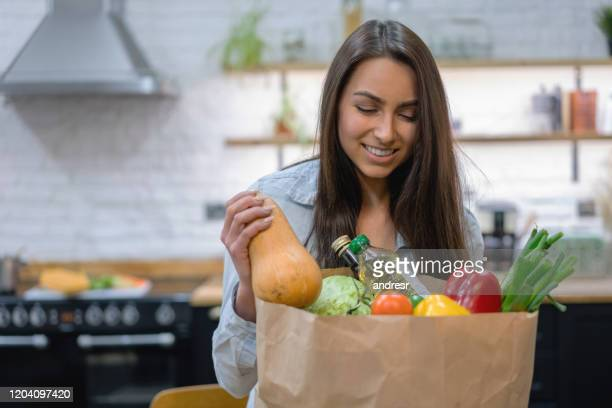 woman at home getting groceries out of a shopping bag - unpacking stock pictures, royalty-free photos & images