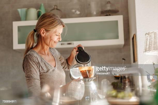 woman at home in kitchen preparing coffee - preparation stock pictures, royalty-free photos & images