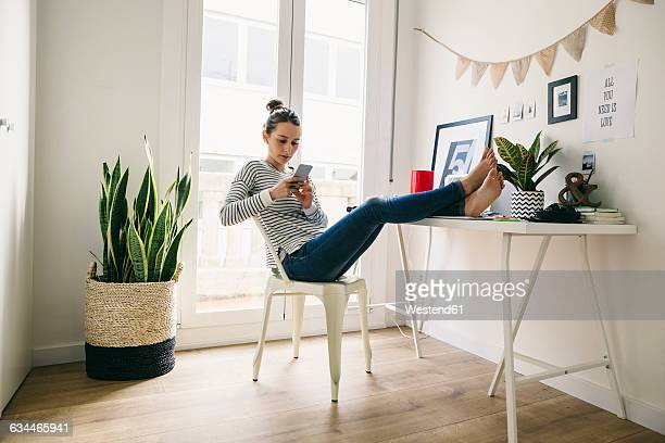 Woman at home laying feet on table looking at cell phone