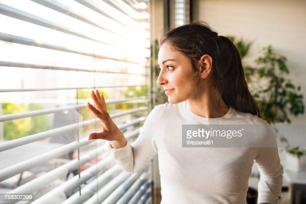 Woman at home looking out of the window