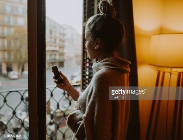 mujer en su casa mirando por la ventana - cyberbullying fotografías e imágenes de stock