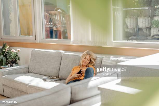 Woman at home on couch using cell phone