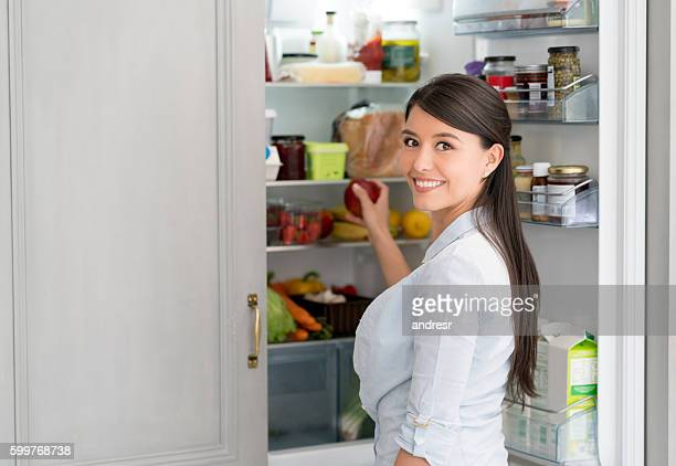 Woman at home opening the fridge