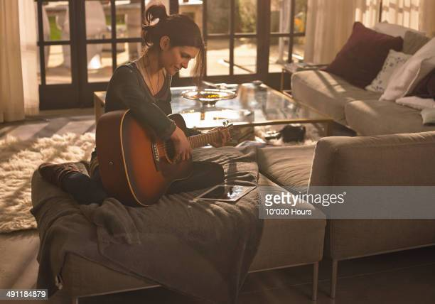 A woman at home playing guitar looking at an iPad