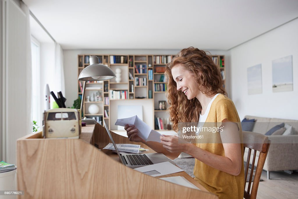 Woman at home reading letter on secretary desk : Stock Photo