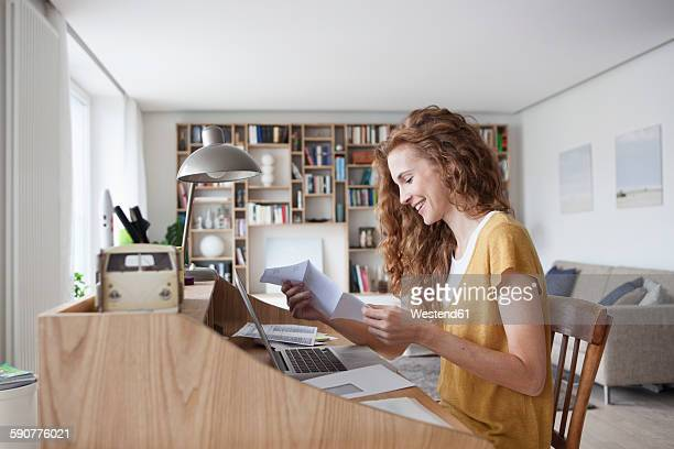 Woman at home reading letter on secretary desk