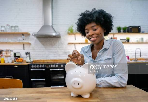 woman at home saving money in a piggybank - currency stock pictures, royalty-free photos & images