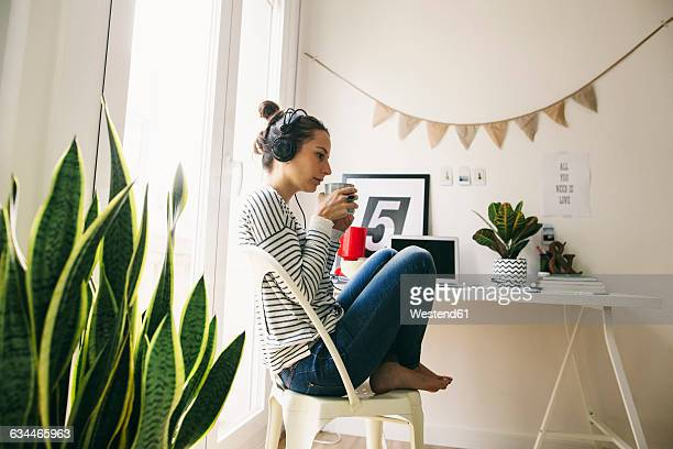 Woman at home sitting at table wearing headphones