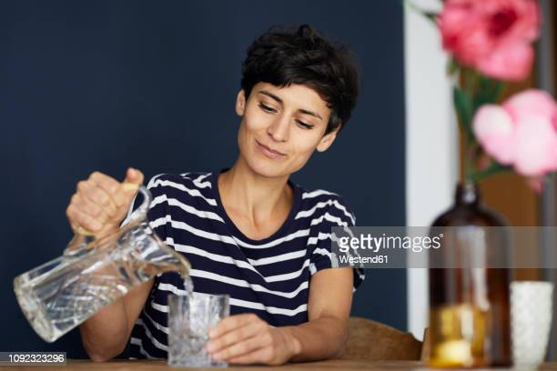 woman at home sitting at wooden table pouring water into glass - trinkwasser stock-fotos und bilder