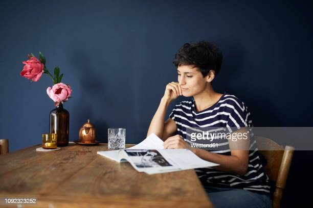 woman at home sitting at wooden table reading a magazine - glass magazine stock photos and pictures