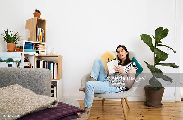 Woman at home sitting on chair looking up