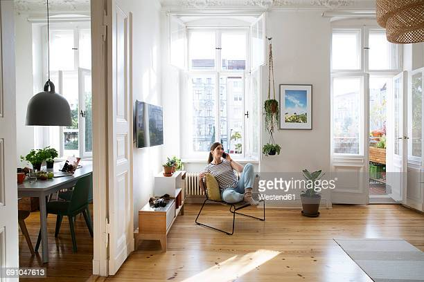 Woman at home sitting on chair talking on cell phone