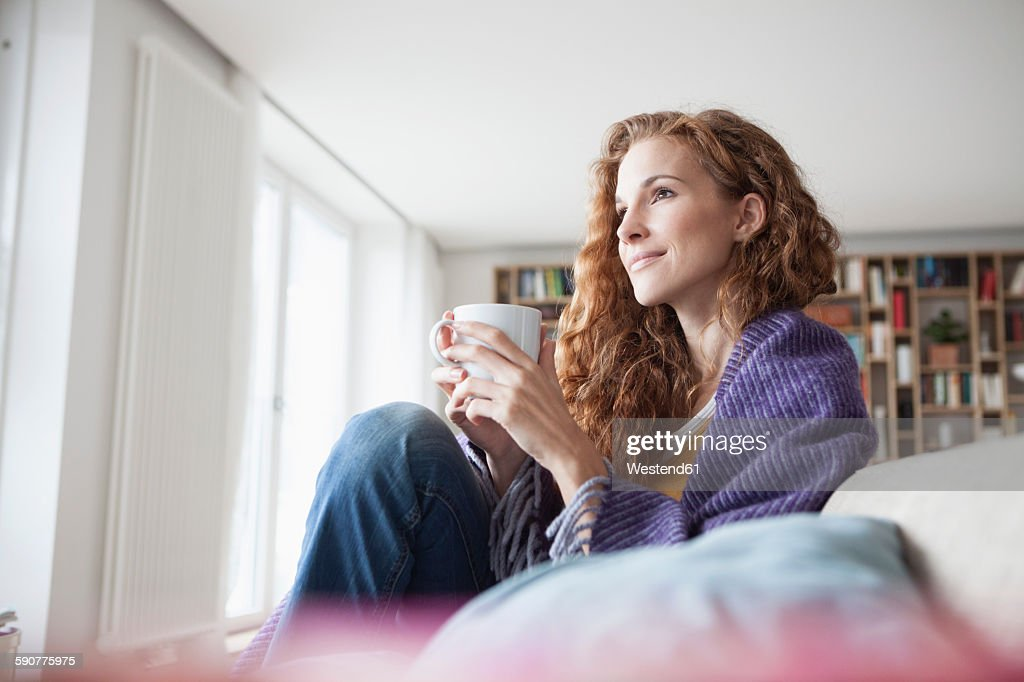 Woman at home sitting on couch holding cup : Stock Photo