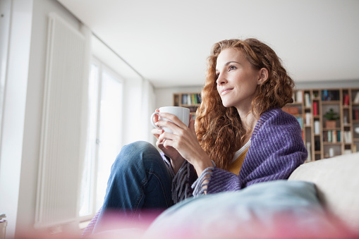 Woman at home sitting on couch holding cup - gettyimageskorea
