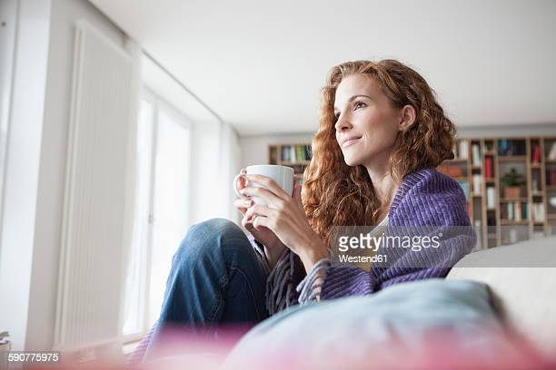 woman at home sitting on couch holding cup - hot tea stock pictures, royalty-free photos & images