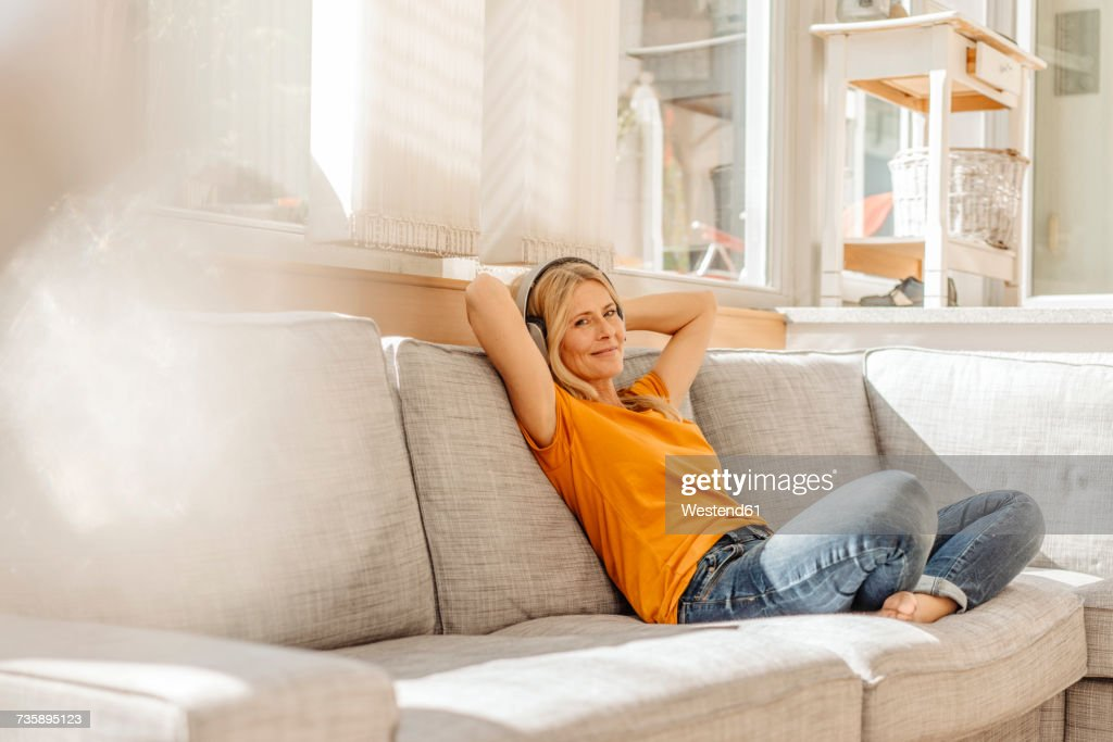 Woman at home sitting on couch wearing headphones : Stock Photo