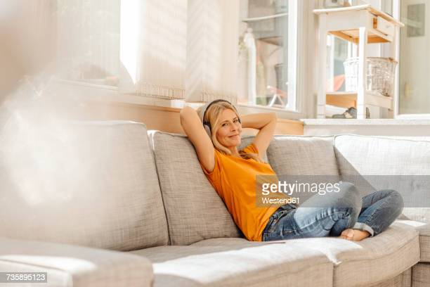 woman at home sitting on couch wearing headphones - gelassene person stock-fotos und bilder