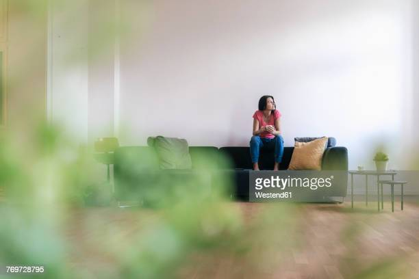 Woman at home sitting on sofa with cup of coffee